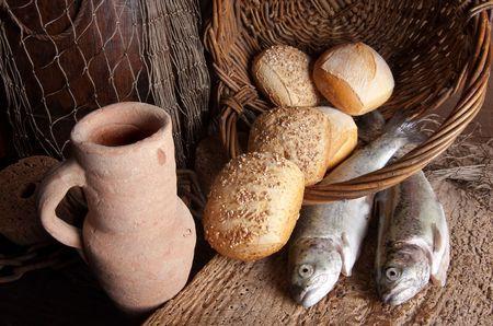 pan y vino: Vintage todav�a vida de una jarra de vino viejo con hogazas de pan y pescado fresco Foto de archivo