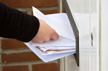 letterbox: Hand putting new mail in a full letter box