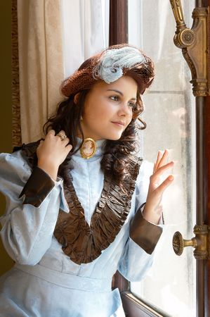 edwardian: Vintage portrait of a victorian lady standing by a castle window. Shot in the antique castle Den Brandt in Antwerp, Belgium (with signed property release for the Castle interiors).