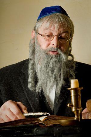 yiddish: L'uomo vecchio con la barba ebraica lettura con un puntatore Torah