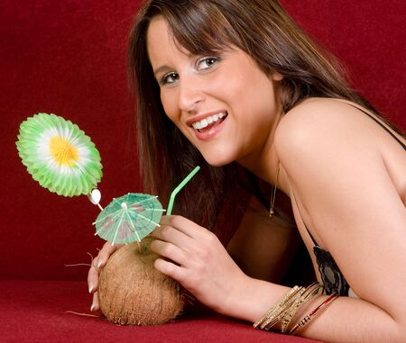 Young woman on a couch drinking a coconut cocktail Stock Photo - 5022575