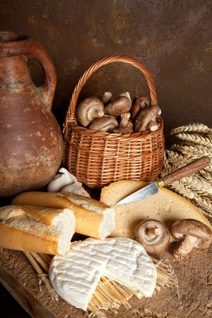 Country still life of rustic bread, cheese and an antique wine jug photo