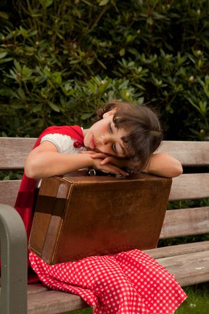 Lonely girl in red sitting on a bench with her suitcase photo