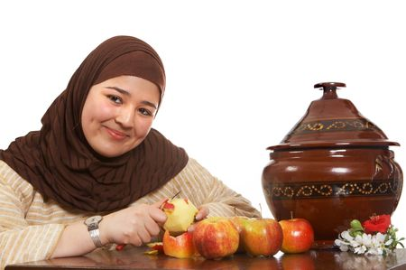 Young smiling islamic woman peeling an apple photo