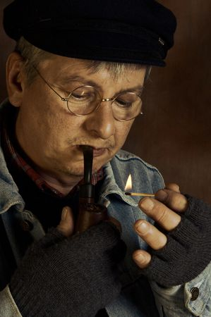 Old farmer lighting his pipe with a match Stock Photo - 5089126