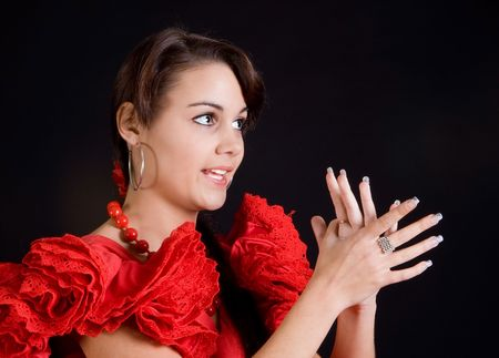 Young Spanish flamenco dancer singing and clapping her hands photo