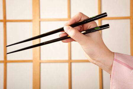 shoji: Hands in kimono sleeve holding chopsticks in front of a japanese shoji sliding window Stock Photo