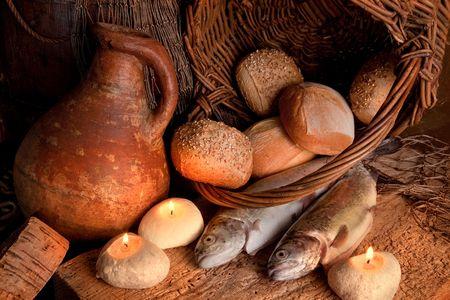 milagro: Dos peces y cinco panes de pan con una vela de luz y una jarra de vino antiguas Foto de archivo