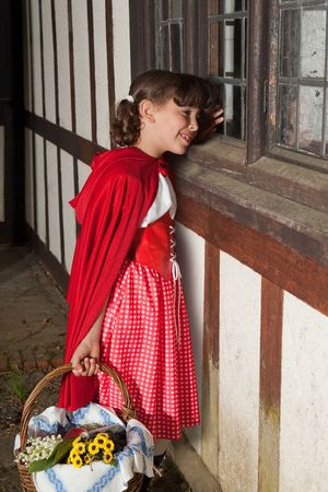 Little red riding hood looking through the window of her grandma's cottage Stock Photo - 5089115