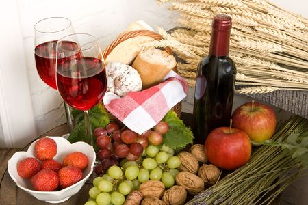 Basket with food and red wine on a barrel photo