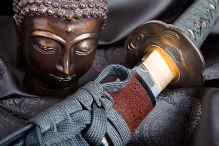 War and peace symbolized by a buddha and a japanese samurai sword photo