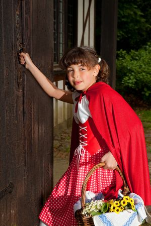 Little red riding hood entering the cottage of her grandmother photo