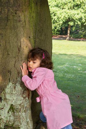 kabouters: Meisje dat haar oor tegen een grote boom, het luisteren naar de kabouters Stockfoto