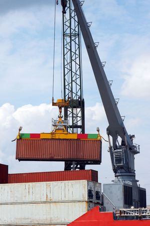 docker: Detail of a large crane carrying one container into a ship (all brand names and logos have been removed)
