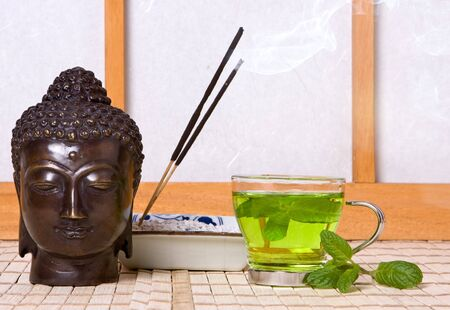 Green tea and lotus incense, with a serene buddha head in bronze Stock Photo - 5185842