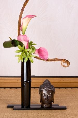Ikebana flower arrangement and buddha photo