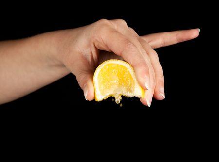squeezed: La mano de una mujer exprimiendo un lim�n amarillo Foto de archivo