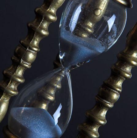 mesure: Bronze hourglass against a black background Stock Photo