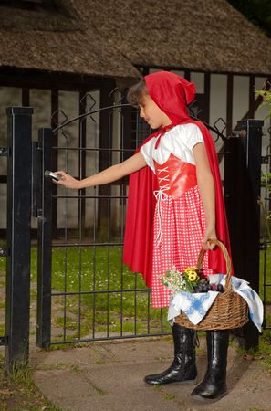 Little red riding hood opening the gate the her grandmother's cottage Stock Photo - 5213848