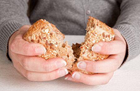 bread loaf: Mani di una donna di rottura e la condivisione del pane Archivio Fotografico