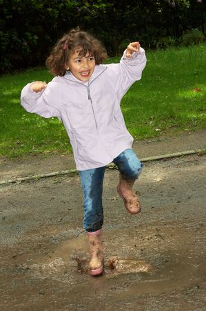 Little girl dancing in a water puddle in the park photo