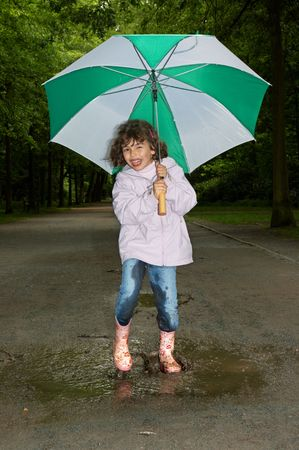 Little girl dancing with her umbrella in a water puddle photo