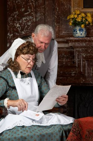 Vintage scene of a Victorian couple reading bad news in a letter.