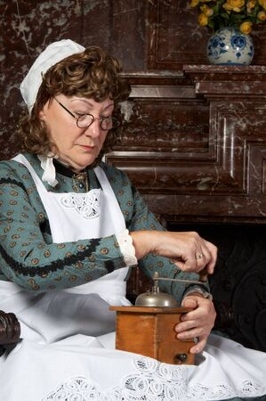 Vintage scene of a victorian woman working with a coffee grinder. Shot in the antique castle Den Brandt in Antwerp, Belgium (with signed property release for the Castle interiors). photo