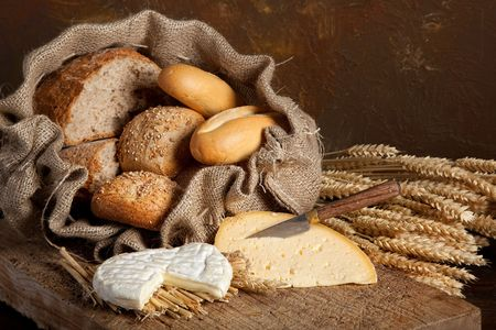 Vintage still life of bread rolls and French cheese photo