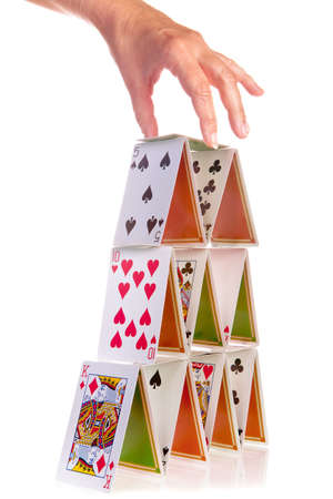 Hand trying to add a fourth floor to a house of cards