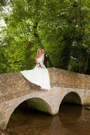 Loving newly wed couple posing on a medieval grunge packhorse bridge Stock Photo - 5343572