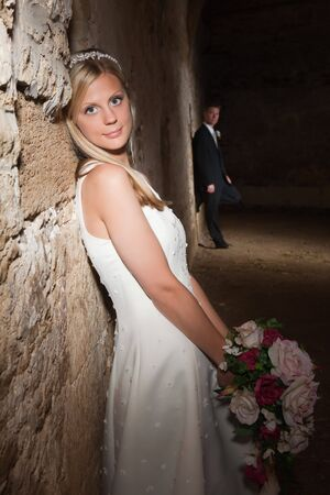 Bride in white posing against a medieval grunge barn wall Stock Photo - 5343575