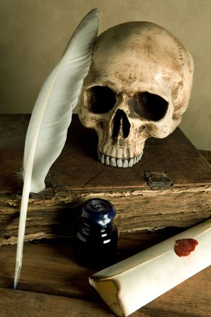 mystic: Skull and antique book on a table with old parchment and quill Stock Photo