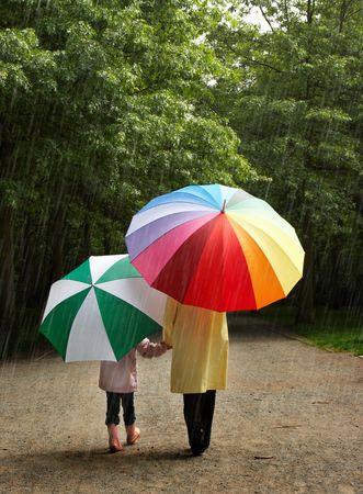 lluvia paraguas: Ni�a y su madre en la lluvia