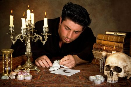 Halloween scene of a man sticking needles in a voodoo doll Stock Photo - 5420715
