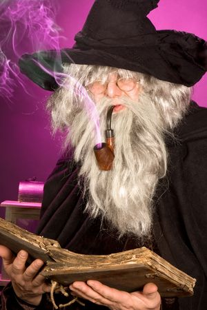 Halloween sorcerer with purple smoke leaving his pipe photo