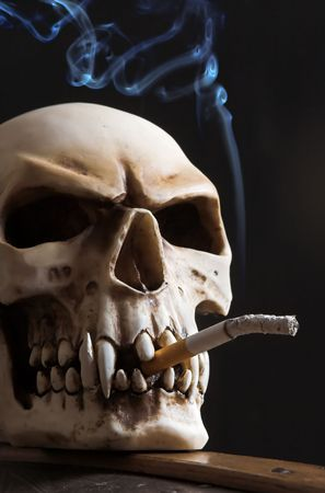 Skull with a cigarette, and blue smoke Stock Photo - 5428876