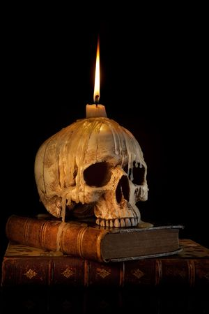 Halloween image with a burning candle on an ancient skull photo
