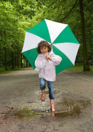 botas de lluvia: Ni�a peque�a que se ejecuta en un charco de agua en el Parque