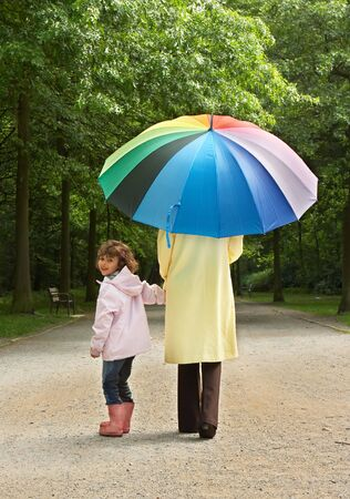 Little girl and her mother walking in the park on a rainy day photo