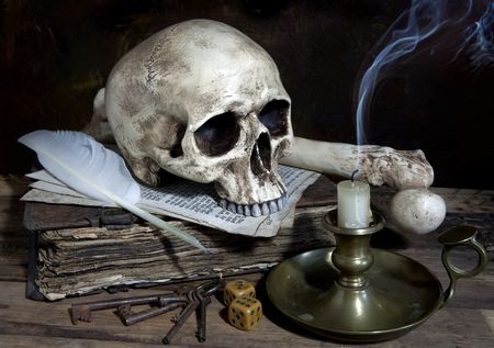 Blown out candle with skull and quill on antique book photo