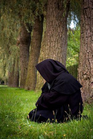 Donkere scene van een zwarte hooded monnik knielen in het bos