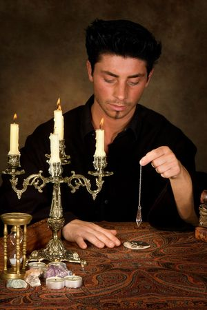 Fortune-teller holding a pendulum above a wedding photo (this photo is model released) Stock Photo - 5446344