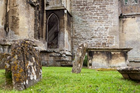 Lichen covered medieval graves of Lacock church in Wiltshire England photo