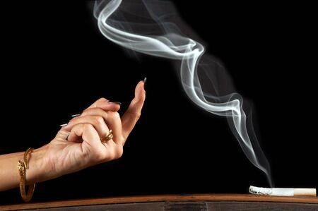 se�al de silencio: Mano de la mujer llamara a un hilo de humo de un sigarette