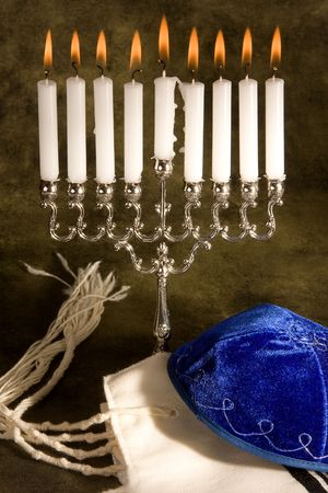 Hanukkah candle-holder, prayer shawl and cap photo