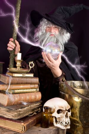 psychic reading: Halloween wizard looking into his glass sphere Stock Photo
