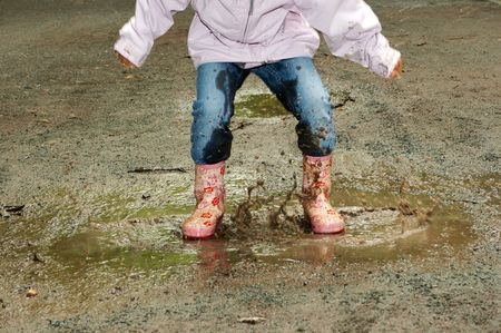 Feet of a little girl jumping into a muddy puddle photo