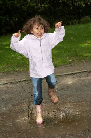 Little girl dancing in the park, splashing in a water puddle photo