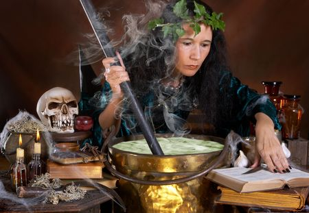 wicca: Halloween witch stirring in green poison soup in her cauldron
